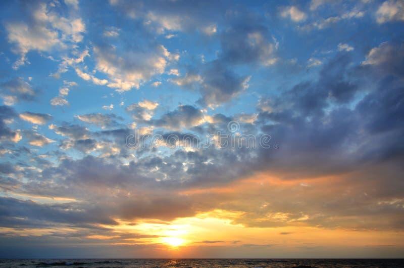 Cielo di stagione Tonalità arancione e blu nuvole e onde marine splendida natura tramonto luminoso fotografia stock libera da diritti
