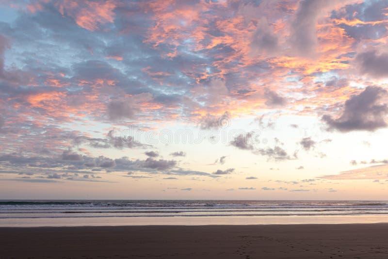 Cielo di tramonto in blu ed arancia con la spiaggia scura nella priorità alta fotografia stock