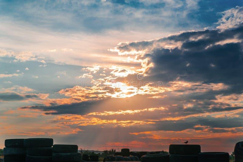 Cielo di tramonto su un mucchio di vecchi pneumatici fotografia stock