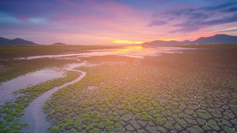 Cielo dramático de la puesta del sol sobre la tierra de la grieta y la pequeña manera del agua foto de archivo libre de regalías