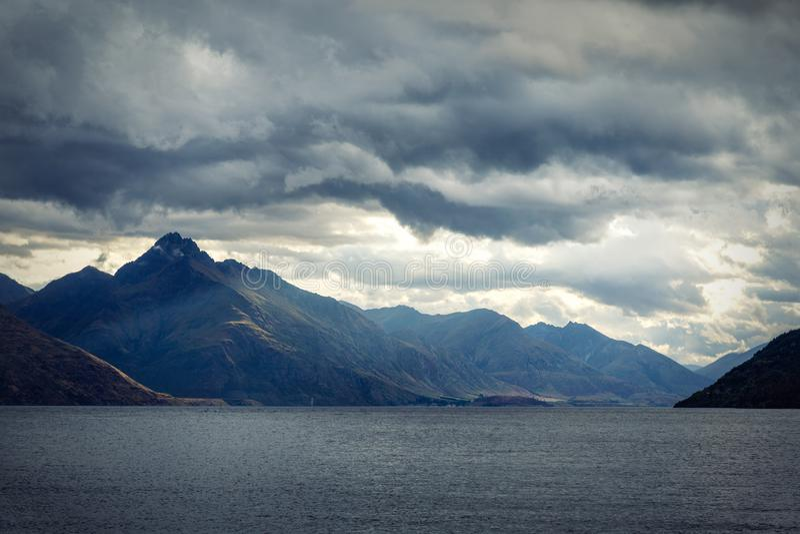 Cielo dramático de la tarde sobre las montañas y el lago Wakatipu foto de archivo