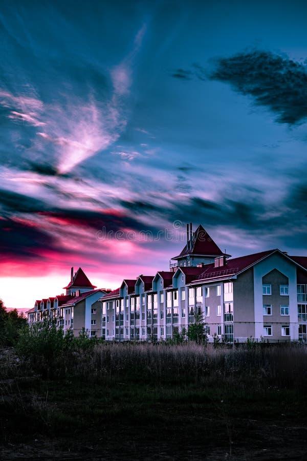 Cielo dramático sobre la casa hermosa en la puesta del sol magenta nublada imágenes de archivo libres de regalías