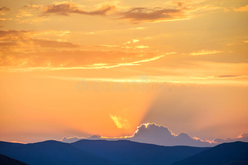 Cielo dramático sobre silueta de la montaña fotografía de archivo