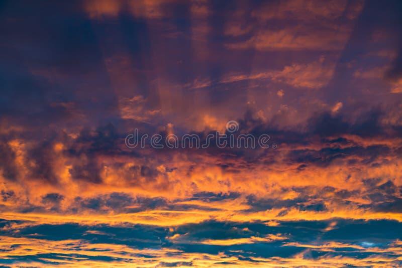 Cielo en la puesta del sol Puesta del sol fantástica colorida - nubes anaranjadas iluminadas por los haces del sol poniente contr imagen de archivo