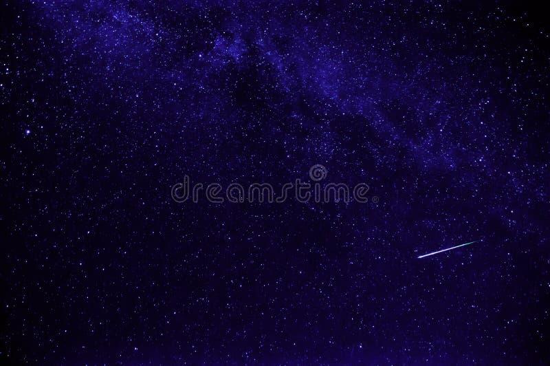 Cielo estrellado de la noche púrpura con la estrella fugaz fotografía de archivo libre de regalías