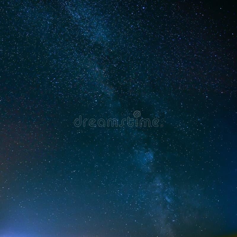 Cielo estrellado de la noche sobre campo y luces amarillas de la ciudad en Backgroun fotografía de archivo libre de regalías