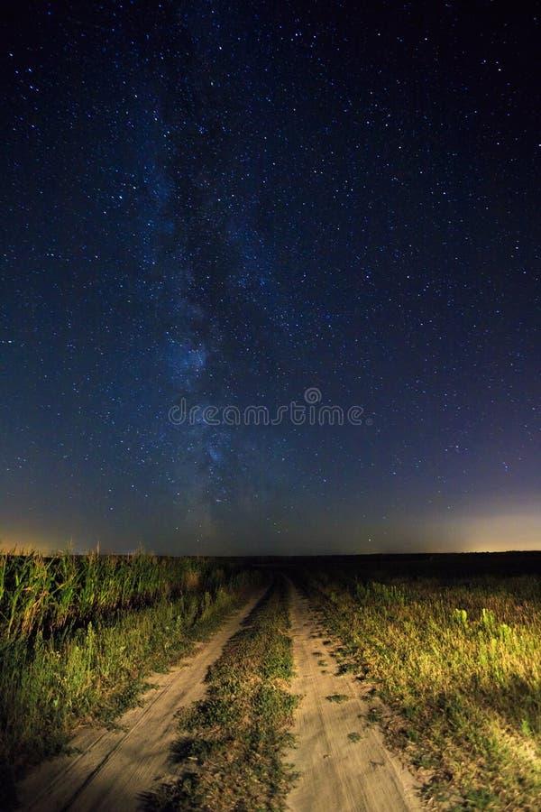 Cielo estrellado de la noche sobre la carretera nacional en campo y campo verde foto de archivo libre de regalías