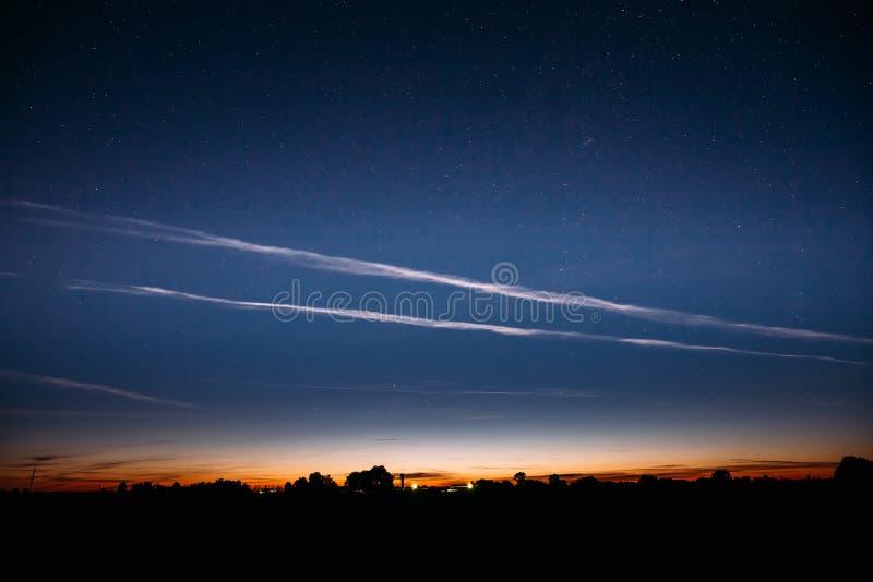 Cielo estrellado de la noche y nubes noctilucientes sobre campo del verano foto de archivo libre de regalías
