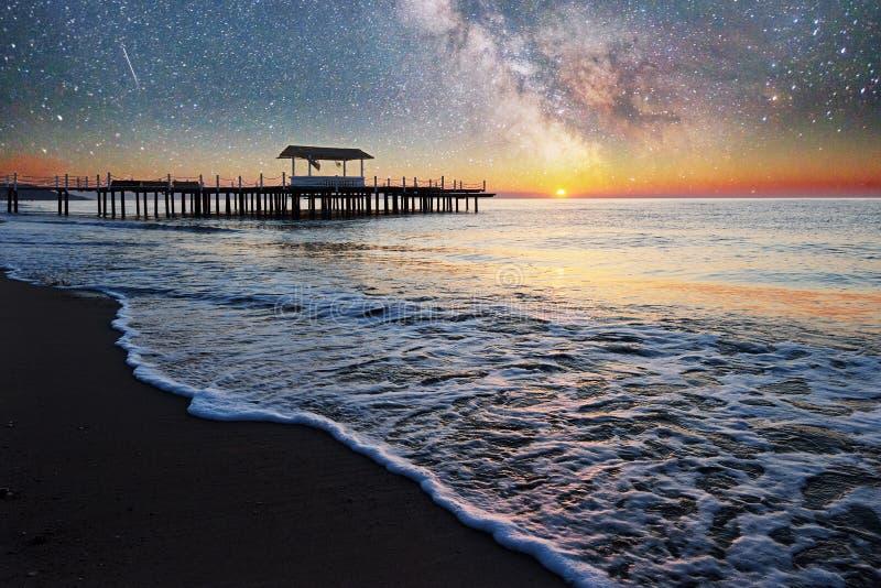 Cielo estrellado fantástico y la vía láctea al embarcadero en el mar, usado al mar del fondo natural Noche romántica imágenes de archivo libres de regalías