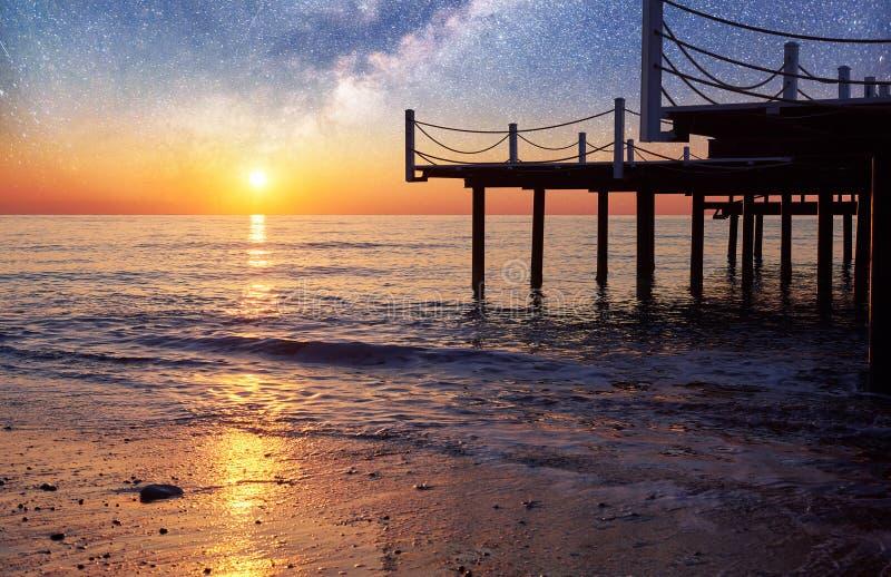 Cielo estrellado fantástico y la vía láctea al embarcadero en el mar, usado al mar del fondo natural Noche romántica imagenes de archivo