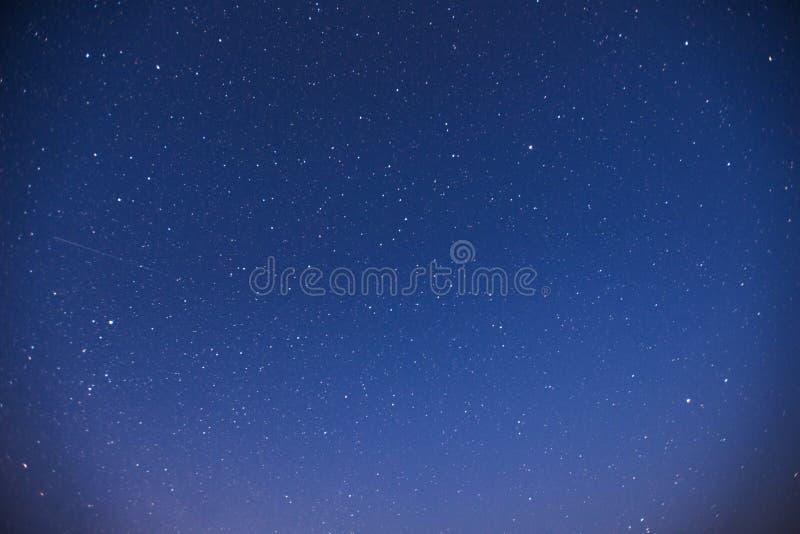 Cielo estrellado Lluvia de meteoritos fantástica del invierno y las montañas coronadas de nieve imagenes de archivo