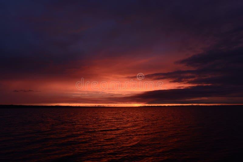 Cielo grigio sul lago con colori brillanti di un tramonto immagini stock libere da diritti