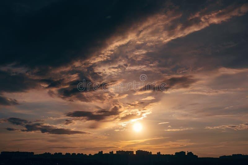 Cielo hermoso de la puesta del sol con las nubes dramáticas sobre siluetas de los edificios de la ciudad foto de archivo libre de regalías