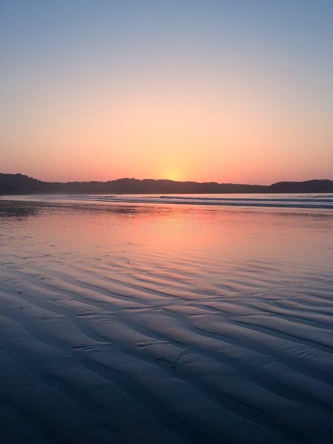 Cielo hermoso de la puesta del sol en la playa - sol de igualación colorido sobre el océano foto de archivo libre de regalías