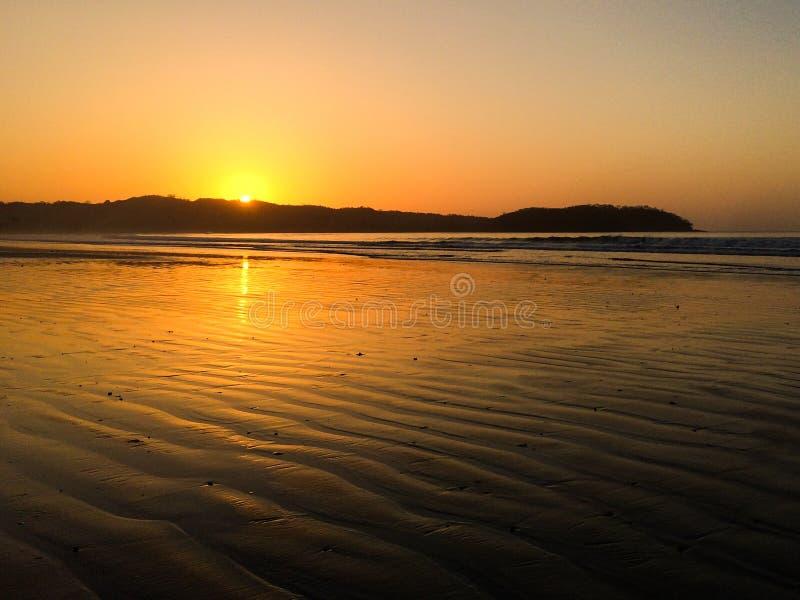 Cielo hermoso de la puesta del sol en la playa - sol de igualación colorido sobre el océano fotografía de archivo