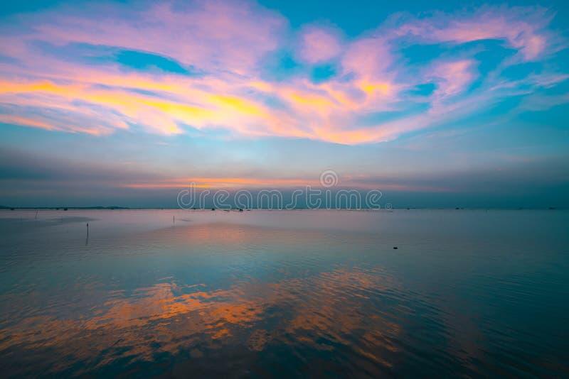 Cielo hermoso de la puesta del sol sobre el mar por la tarde Cielo y púrpura azules, naranja, y nubes amarillas Cielo y nubes dra fotografía de archivo libre de regalías