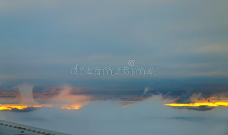Cielo hermoso de la puesta del sol sobre las nubes con la visión dramática desde el aeroplano fotografía de archivo