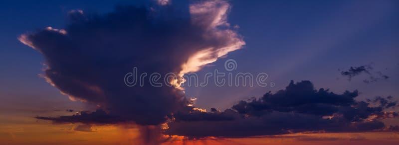 Cielo hermoso en la puesta del sol con una nube enorme en colores anaranjado oscuro y azul marino imagenes de archivo