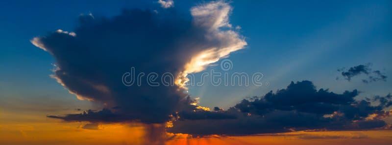 Cielo hermoso en la puesta del sol con una nube enorme en colores anaranjado oscuro y azul marino imágenes de archivo libres de regalías