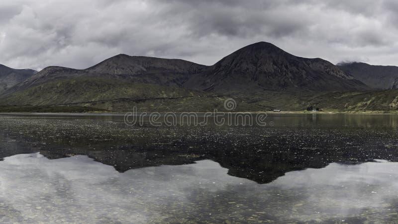 Cielo lunatico sopra i picchi di montagna che riflettono nella superficie del lago fotografia stock libera da diritti