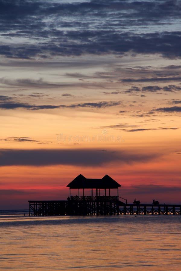 Cielo multicolor en puesta del sol tropical con la silueta del embarcadero imagen de archivo