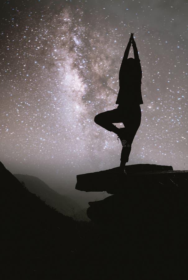 Cielo nocturno colorido con las estrellas y la silueta de una yoga derecha de la muchacha en la piedra foto de archivo