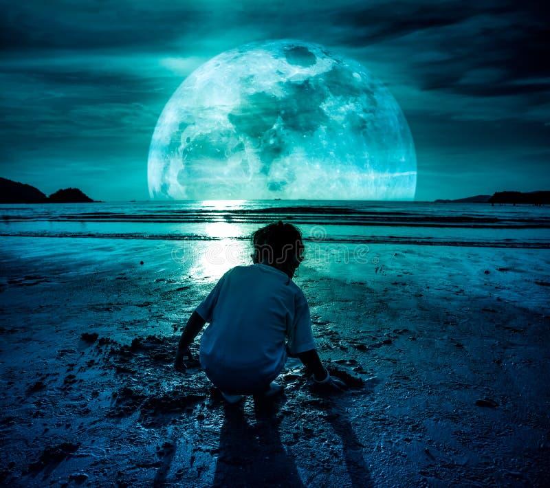 Cielo nocturno con la luna estupenda Muchacha que cava en arena Concepto de conec fotos de archivo