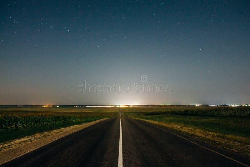 Cielo nocturno con las estrellas sobre los campos de la carretera y de maíz fotos de archivo libres de regalías