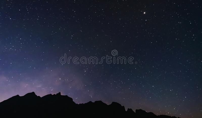 Cielo nocturno lleno de estrellas y de vía láctea, con la montaña de la silueta fotos de archivo