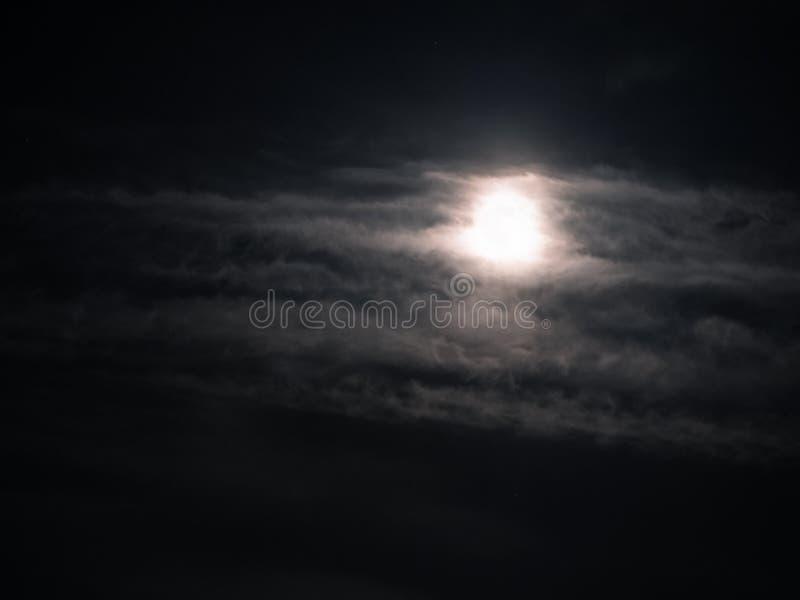 Cielo nocturno nublado con un brillo de la Luna Llena brillante imagen de archivo