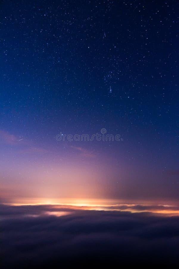 Cielo nocturno sobre la ciudad que tiene baño en niebla imagenes de archivo