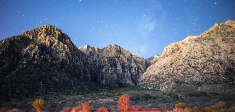 Cielo nocturno y vía láctea con las estrellas sobre neveda rojo del barranco del rock foto de archivo