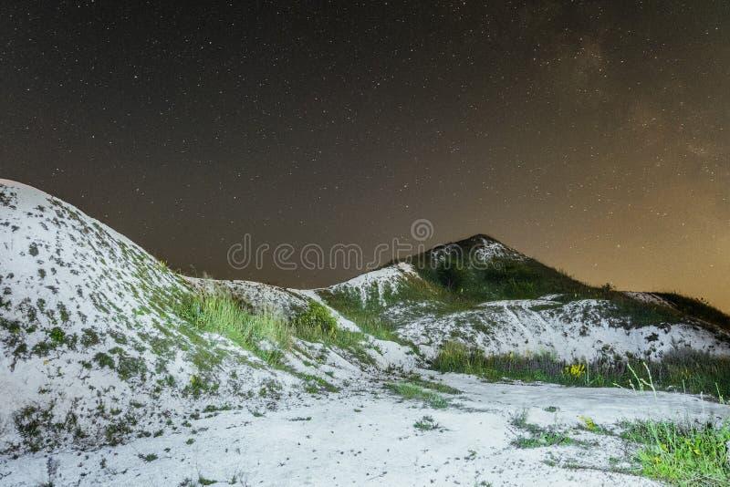 Cielo notturno stellato sopra le colline cretacee bianche Paesaggio naturale di notte con le creste del gesso immagine stock
