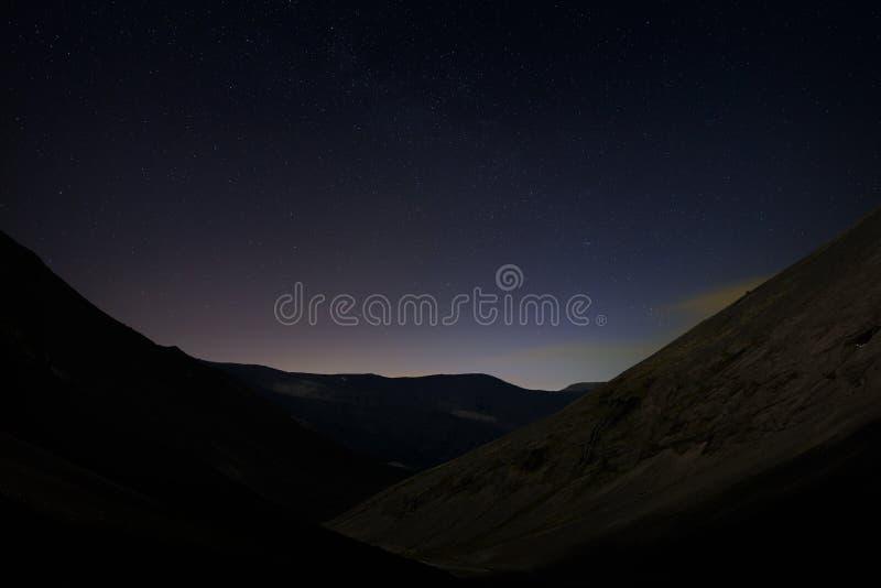 Cielo notturno stellato sopra una valle della montagna immagine stock