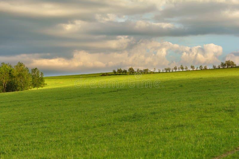 Cielo nublado azul sobre las colinas verdes y los árboles distantes imagenes de archivo