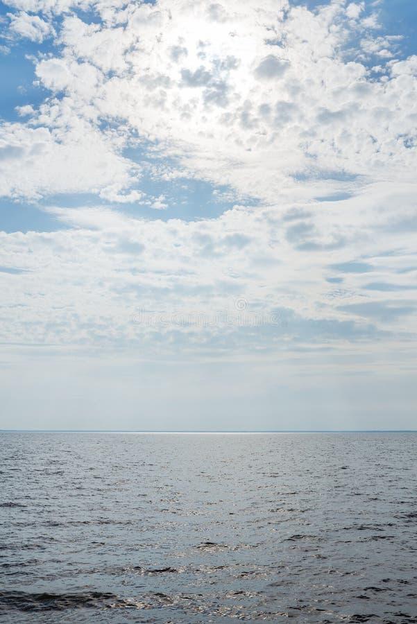 Cielo nublado azul sobre un río ancho imagen de archivo