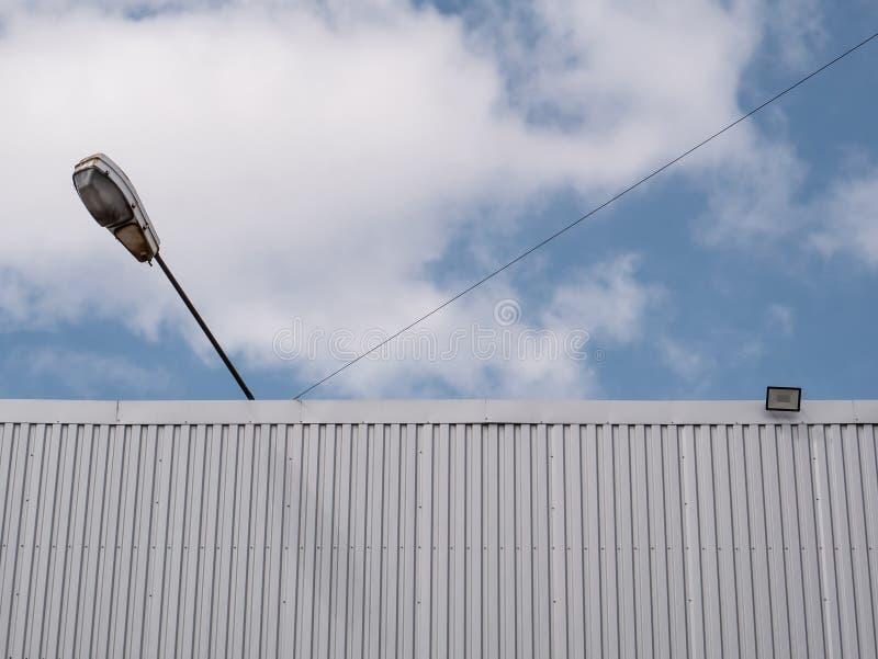 Cielo nublado azul Superficie incons?til del acero galvanizado Pared del edificio industrial hecha de la hoja de metal acanalada fotografía de archivo