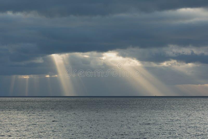 Cielo nublado con los rayos del sol en el mar abierto fotografía de archivo libre de regalías