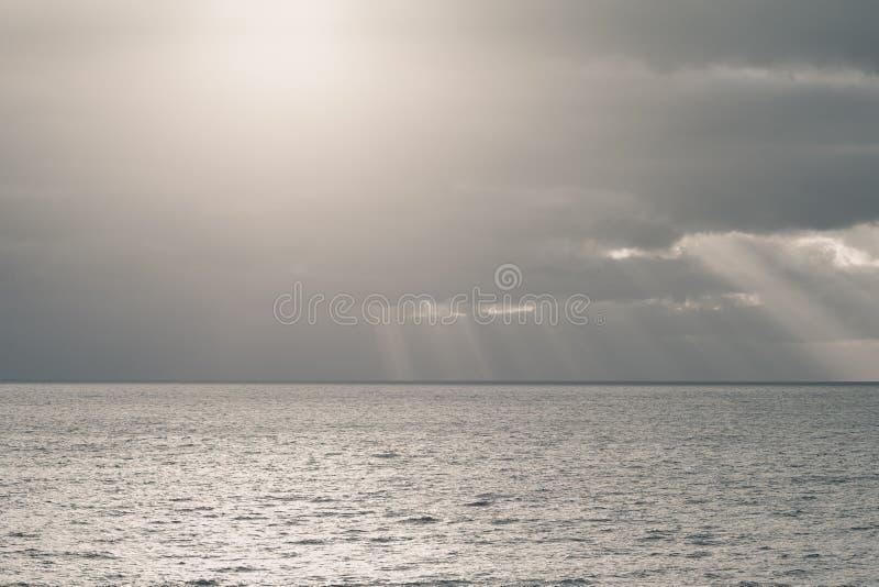Cielo nublado con los rayos del sol en el mar abierto imagenes de archivo