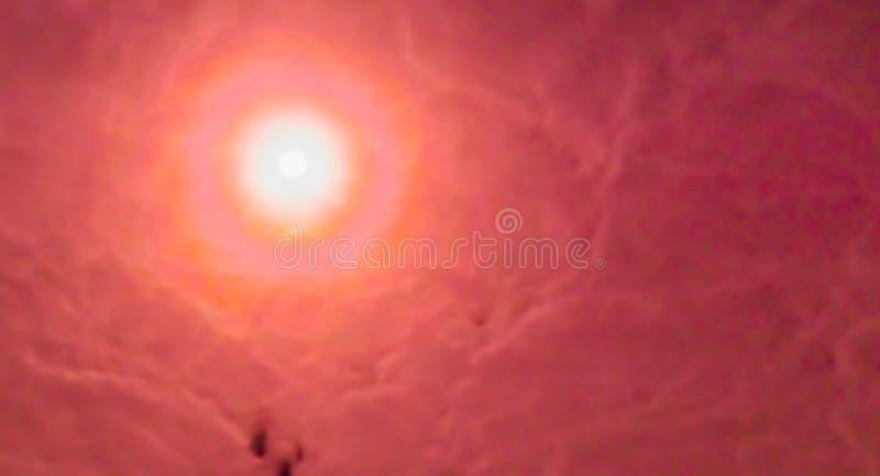 Cielo nublado rojo con un sol brillante que brilla a través del fondo de las nubes, esperanzado y de la inspiración fotografía de archivo libre de regalías