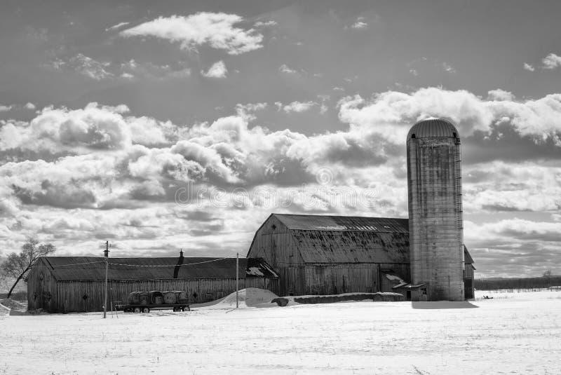 Cielo nublado sobre granero y silo imagenes de archivo