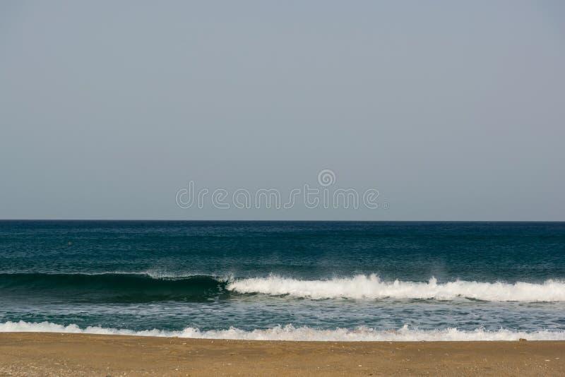 Cielo nublado, viento y ondas en una playa arenosa del mar imagen de archivo