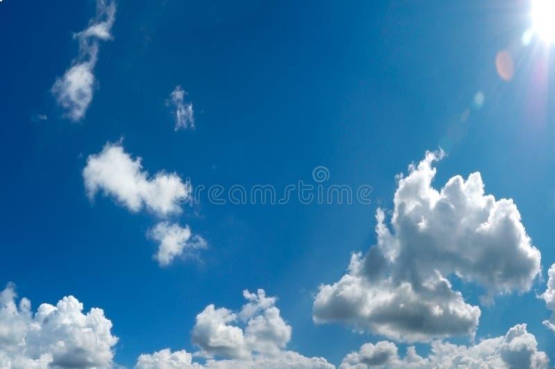 Cielo nuvoloso blu con il sole immagine stock