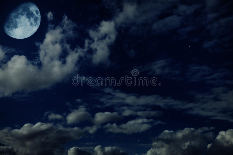 Cielo nuvoloso blu di notte con le stelle e una luna fotografia stock libera da diritti