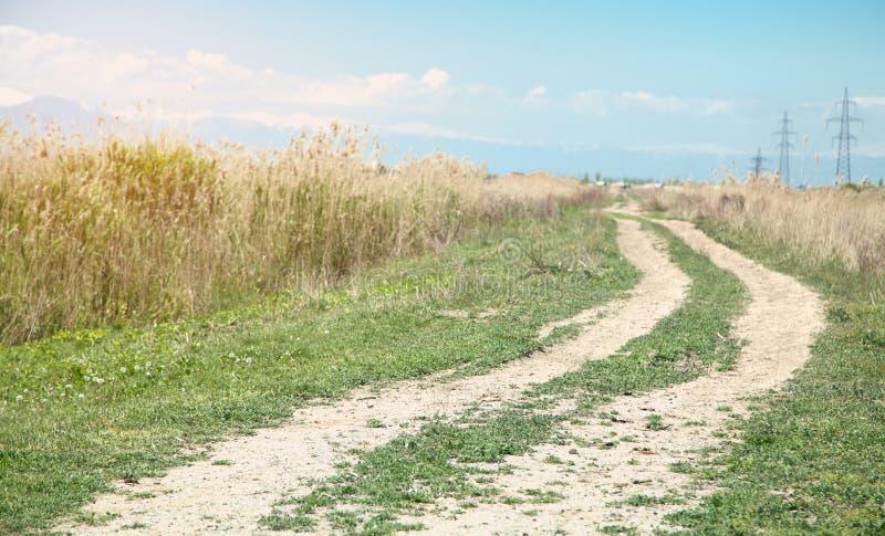 cielo nuvoloso della strada del campo Il tempo di primavera? ? aumentato foglie, sfondo naturale immagini stock