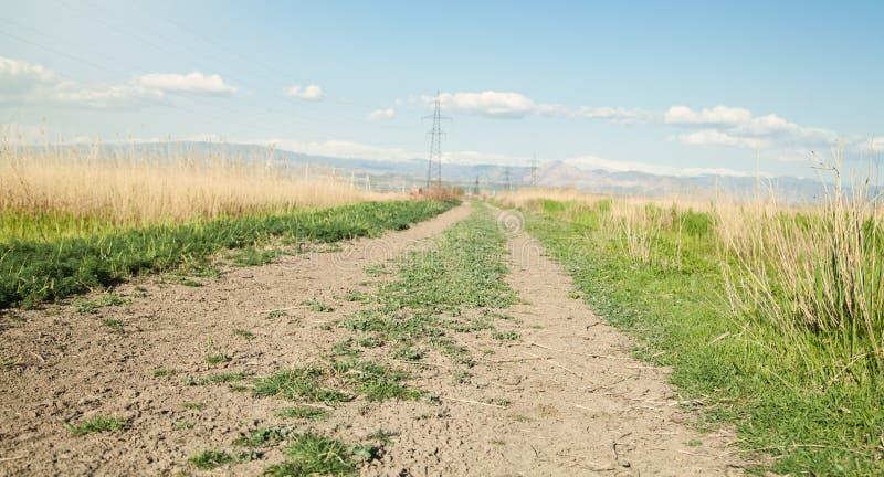 cielo nuvoloso della strada del campo Il tempo di primavera? ? aumentato foglie, sfondo naturale fotografia stock