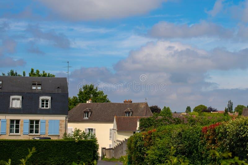 Cielo nuvoloso e di contrapposizione blu sopra un villaggio europeo Case di campagna francesi Barriera e lotti di pianta giù immagine stock