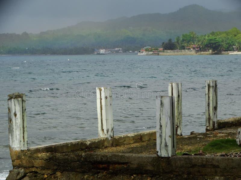 Cielo nuvoloso ed arcobaleno sopra l'isola tropicale fotografia stock libera da diritti