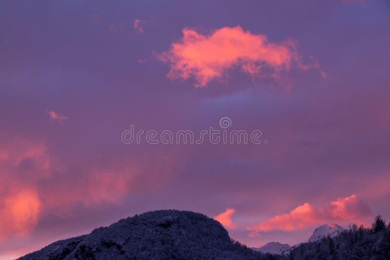 Cielo nuvoloso rosso sopra le montagne fotografie stock