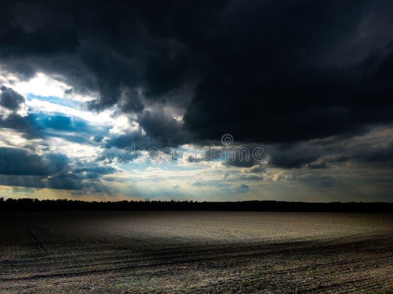 Cielo nuvoloso scuro con lustro del sole sul campo in atmosfera scura fotografie stock